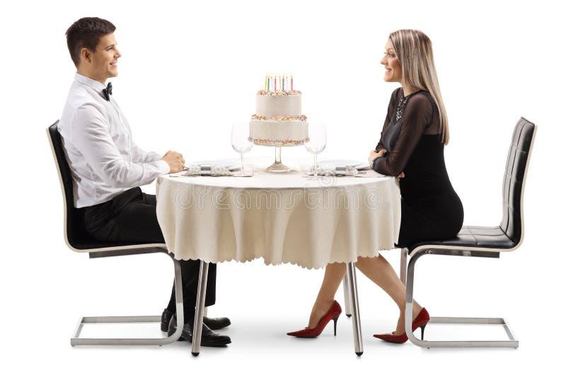 Hombre joven y mujer que celebran un cumpleaños en un restaurtant con una torta en una tabla imagen de archivo libre de regalías