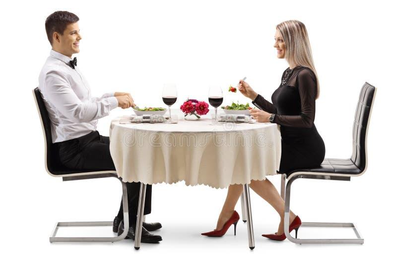 Hombre joven y mujer que comen la ensalada en una tabla imágenes de archivo libres de regalías