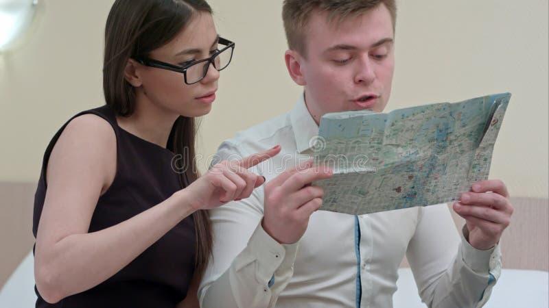 Hombre joven y mujer que comprueban el mapa, hablando, vacaciones de familia de planificación foto de archivo libre de regalías