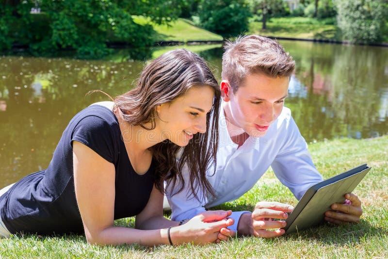 Hombre joven y mujer que mienten en el agua Ipad de lectura fotografía de archivo