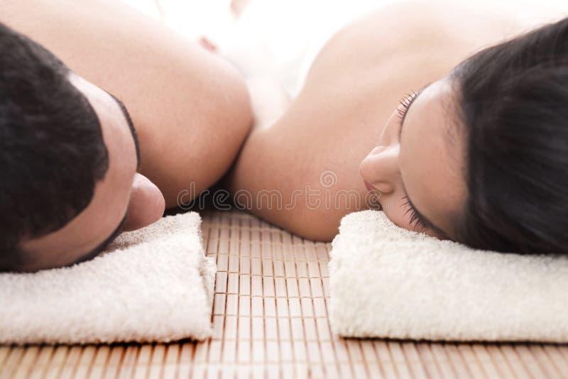 Hombre joven y mujer que mienten en la toalla para tomar el balneario foto de archivo