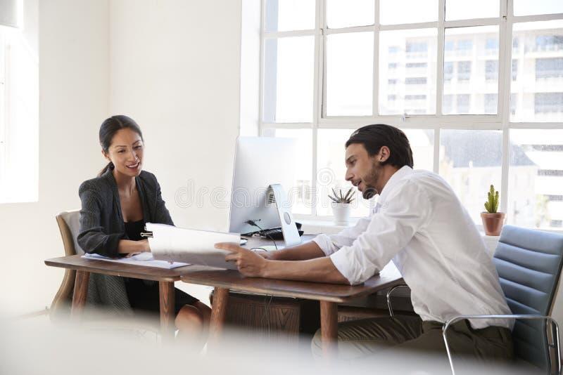 Hombre joven y mujer que miran documentos a través de los escritorios de oficina imagen de archivo