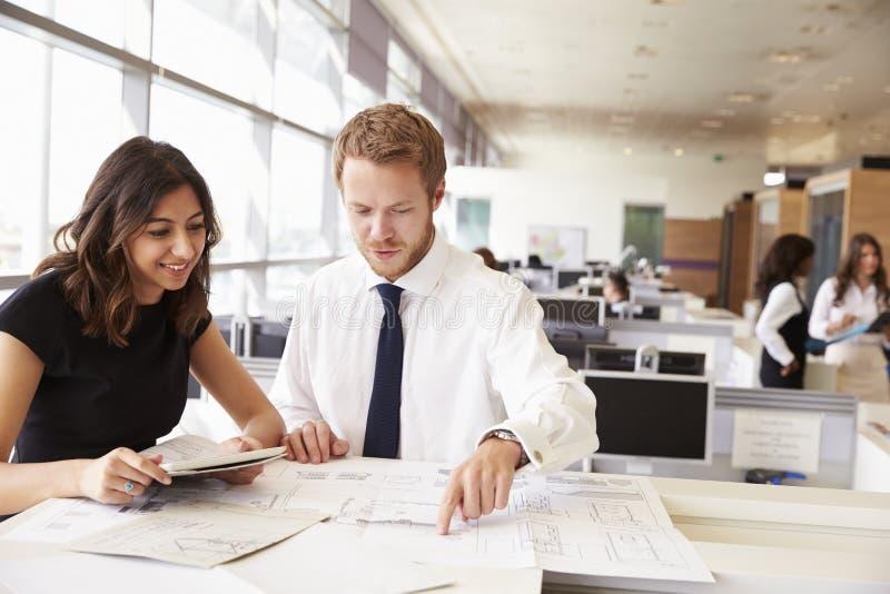 ¿Hombre joven y mujer que trabajan junto en arquitecto? oficina de s imagen de archivo