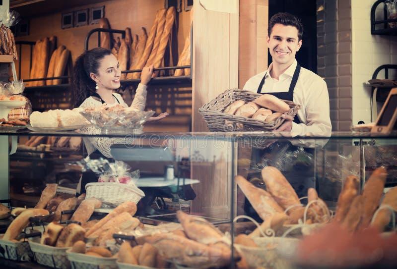 Hombre joven y mujer que venden los pasteles y los panes fotografía de archivo