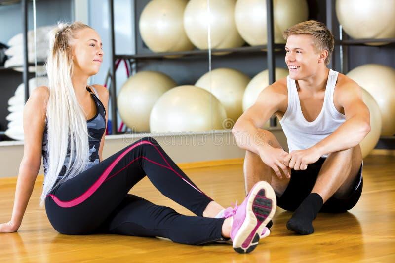 Hombre joven y mujer sonrientes que se sientan en gimnasio foto de archivo libre de regalías