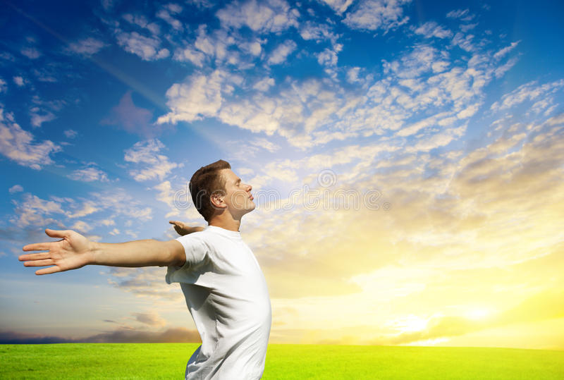 Hombre joven y puesta del sol imagen de archivo