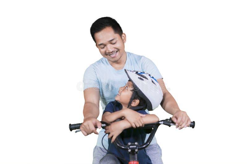 Hombre joven y su bicicleta del montar a caballo del hijo junto fotografía de archivo libre de regalías