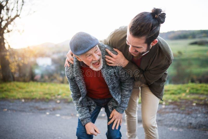 Hombre joven y su padre mayor en un paseo en la naturaleza, riendo imagen de archivo