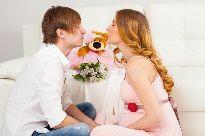 Hombre joven y un beso de la mujer embarazada imagen de archivo libre de regalías