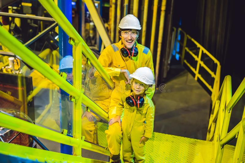 Hombre joven y un ni?o peque?o est?n ambos en un uniforme amarillo, vidrios, y el casco en un ambiente industrial, aceite del tra foto de archivo libre de regalías