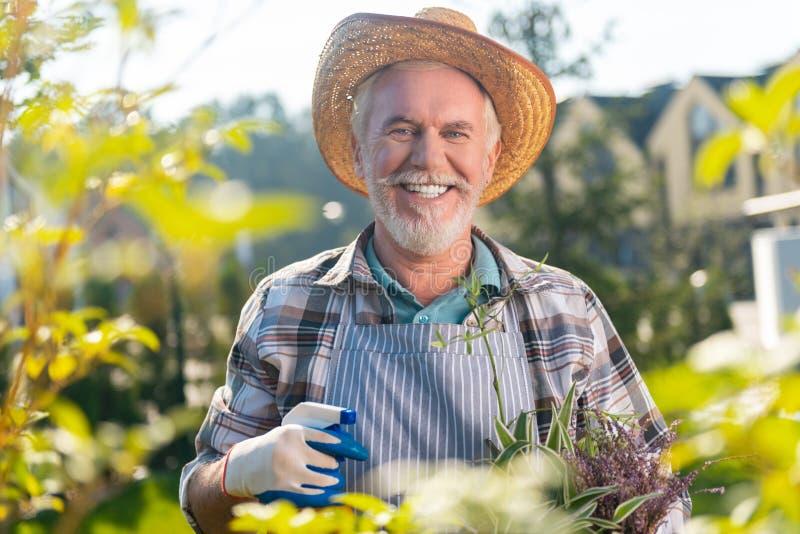 Hombre jubilado motivado implicado que disfruta de un día en el jardín imagenes de archivo