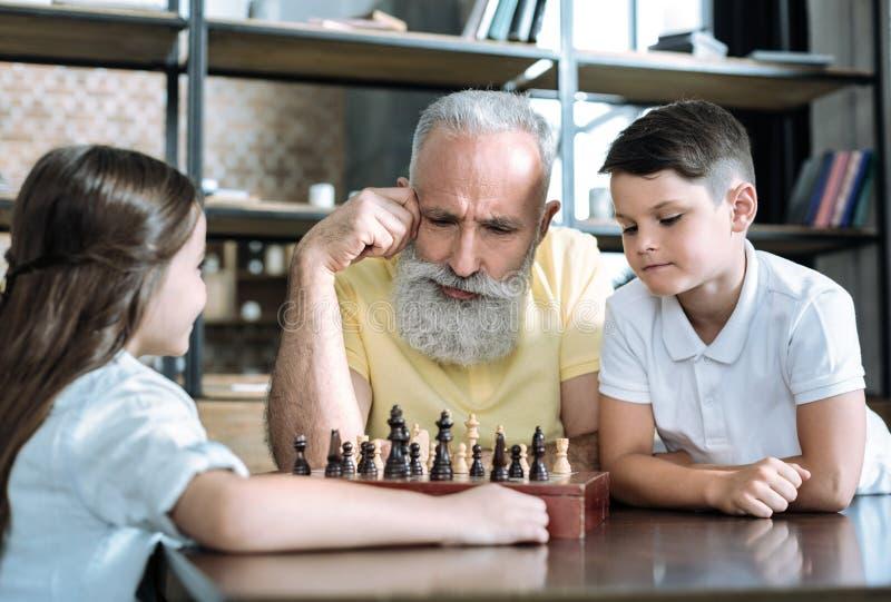 Hombre jubilado pensativo que juega a ajedrez con los nietos imagenes de archivo