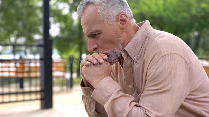 Hombre jubilado pensativo que se sienta en banco con las manos en la barbilla, decisión, problemas foto de archivo