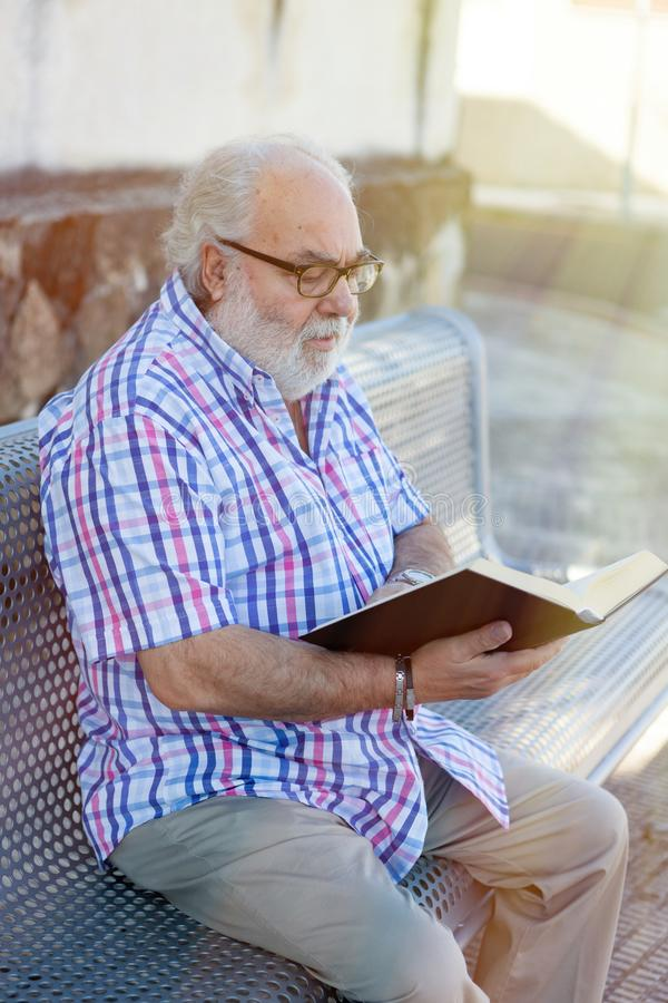Hombre jubilado que lee un libro imagenes de archivo