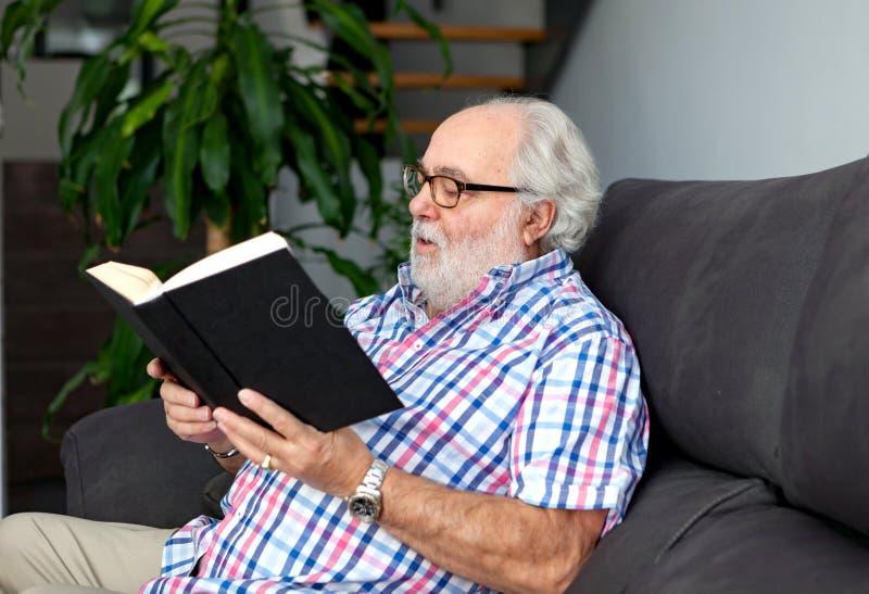 Hombre jubilado que lee un libro en su hogar imagen de archivo libre de regalías