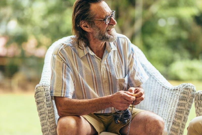 Hombre jubilado que se relaja en la butaca fotos de archivo