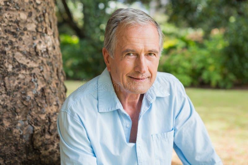 Hombre jubilado sonriente que se sienta en tronco de árbol foto de archivo