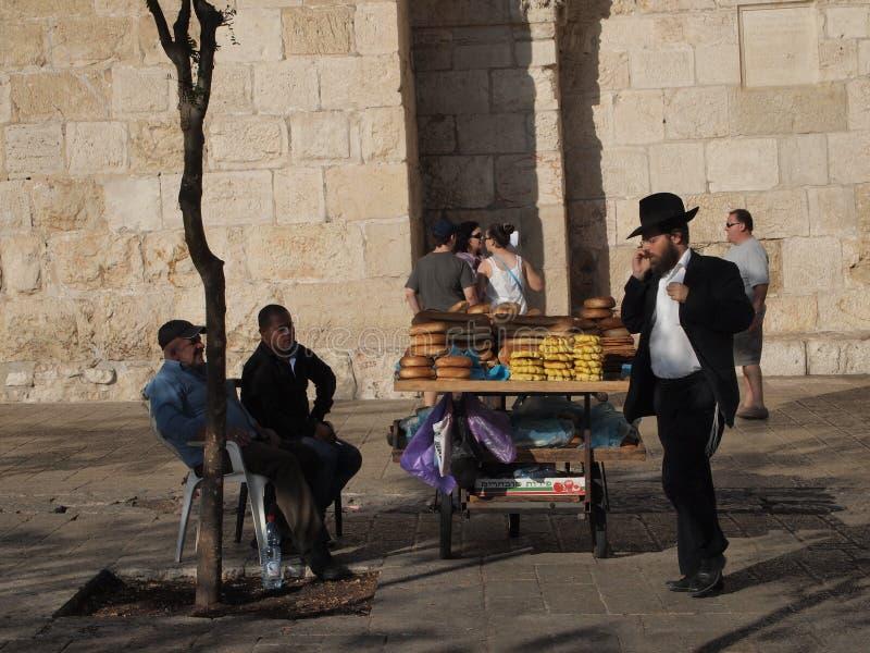 Hombre judío en el teléfono del cel y el vendedor del pan en Jerusalén fotografía de archivo