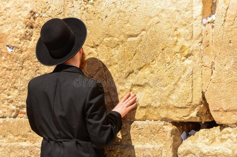 Hombre jud?o ortodoxo que ruega en la pared occidental en Jerusal?n, Israel fotos de archivo