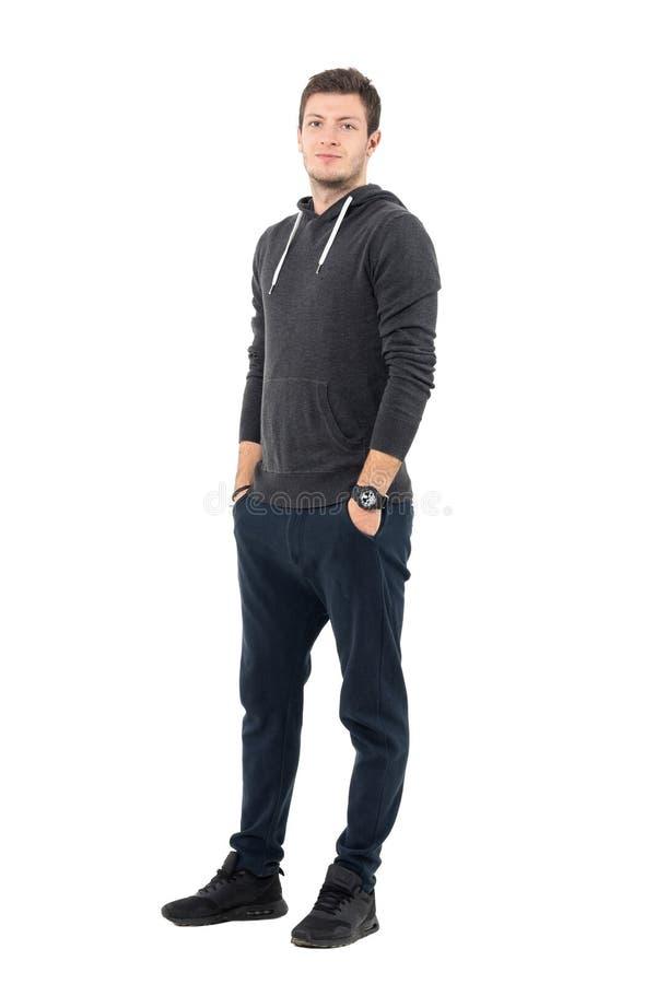 Hombre juguetón joven relajado sonriente en sudadera con capucha con las manos en bolsillos imagen de archivo