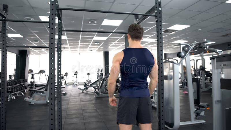 Hombre juguetón que calienta antes del entrenamiento del gimnasio, forma de vida de la aptitud, levantamiento de pesas foto de archivo