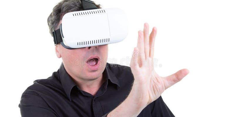 Hombre juguetón que se entretiene que juega a los videojuegos usando los vidrios virtuales aislados en el fondo blanco foto de archivo libre de regalías