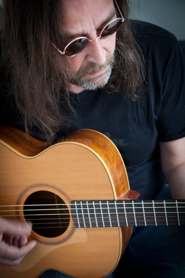 Hombre largo del pelo con las gafas de sol que tocan una guitarra fotografía de archivo libre de regalías