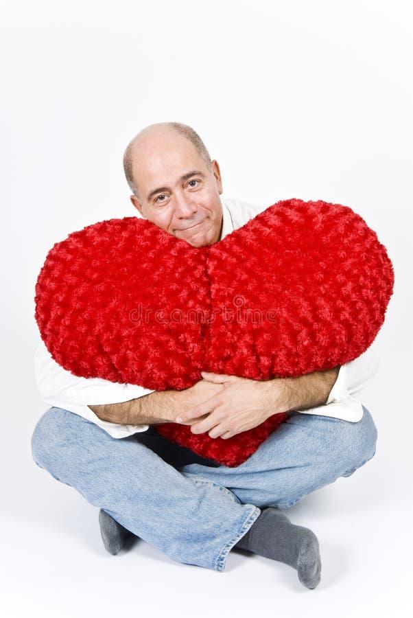 Hombre latino con un corazón rojo imagenes de archivo