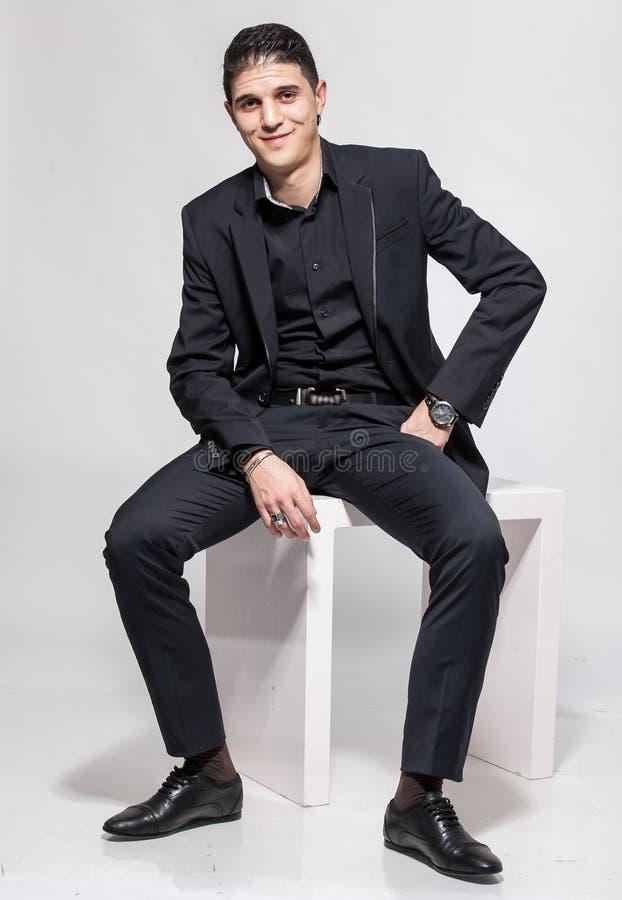 Hombre latino en el traje negro que se sienta en la silla blanca y la sonrisa foto de archivo libre de regalías