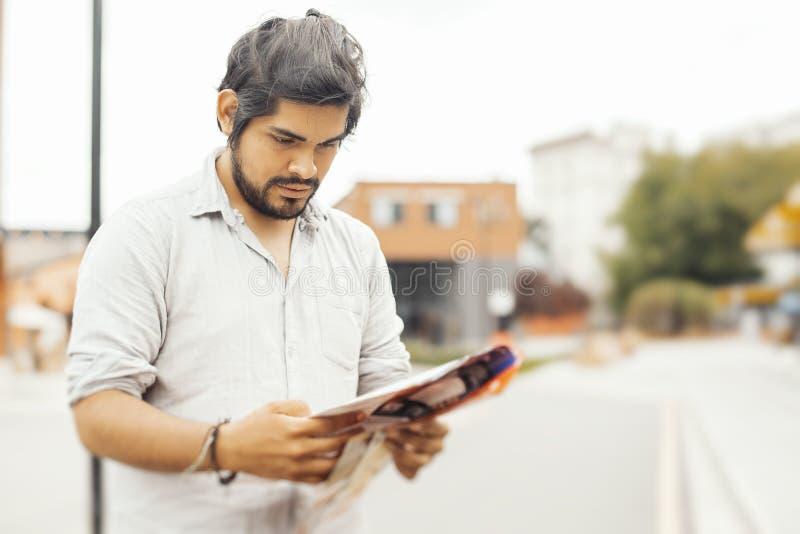 Hombre latino moreno pensativo atractivo que mira el mapa foto de archivo