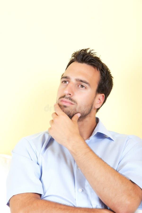 Hombre latino pensativo en su sala de estar imagenes de archivo