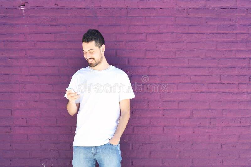 Hombre latino que mecanografía en su teléfono foto de archivo libre de regalías