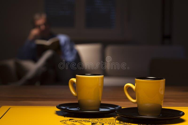 Hombre leyendo en un salón foto de archivo