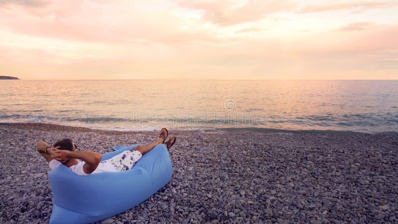 Hombre libre que se relaja en la playa, disfrutando de la opinión del paisaje marino, teniendo resto el vacaciones imagen de archivo libre de regalías