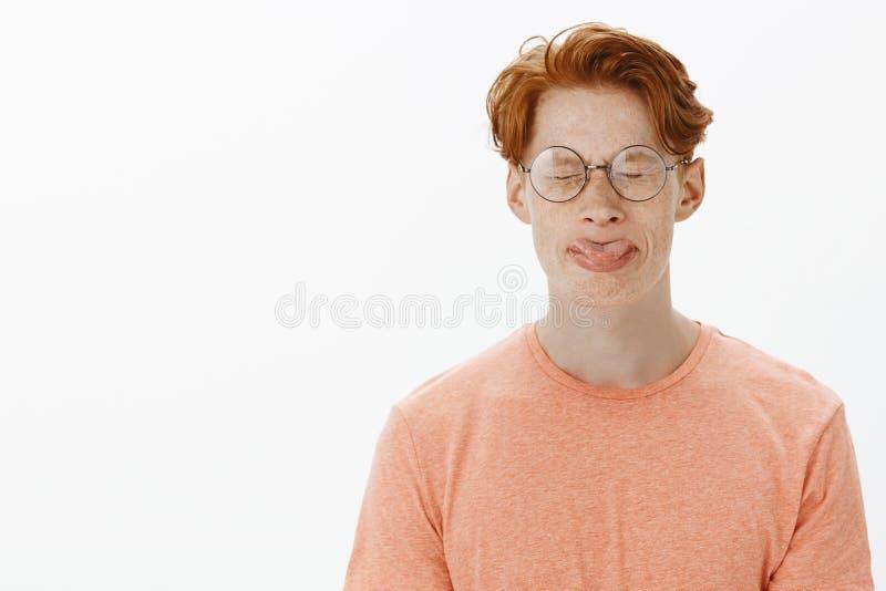 Hombre lindo y divertido del pelirrojo con las pecas y corte de pelo elegante en los vidrios redondos que pegan hacia fuera la le imagenes de archivo