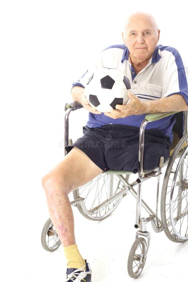 Hombre lisiado en sillón de ruedas con el balón de fútbol fotos de archivo libres de regalías