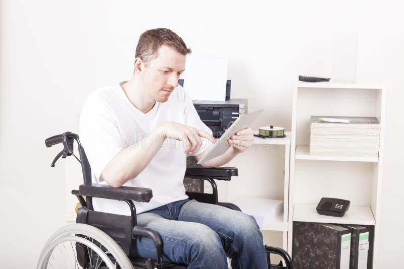 Hombre lisiado en silla de ruedas en el trabajo foto de archivo libre de regalías