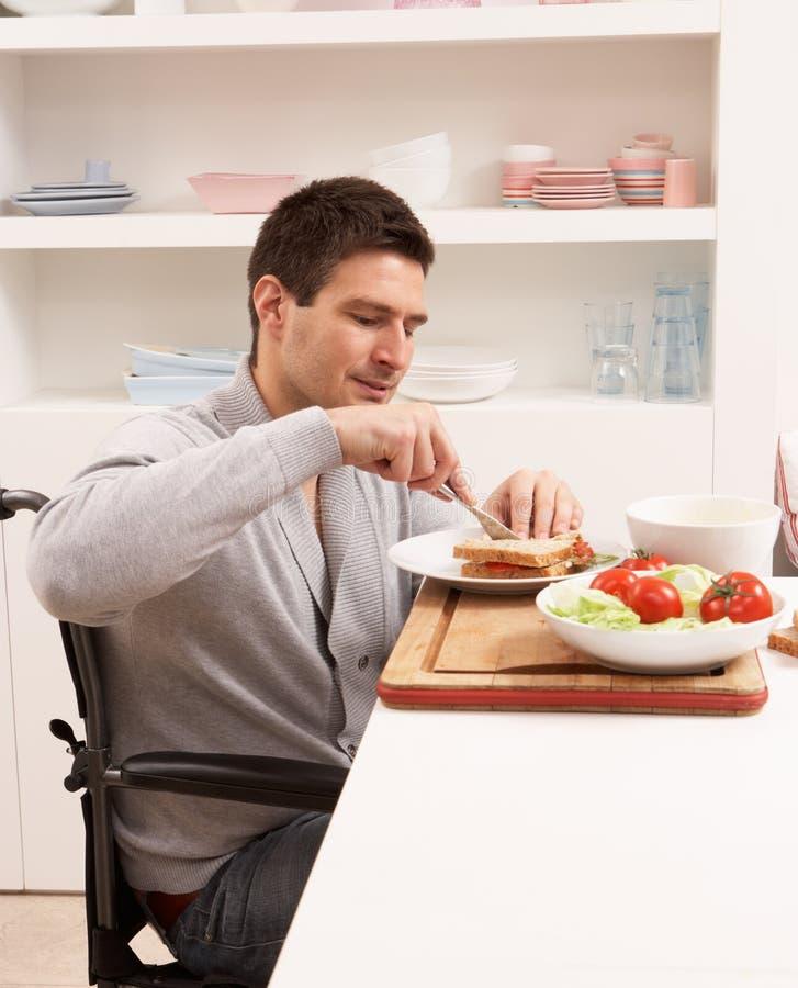 Hombre lisiado que hace el emparedado en cocina imagen de archivo