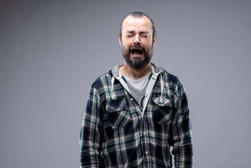Hombre lloroso desgraciado que se lamenta y que llora foto de archivo