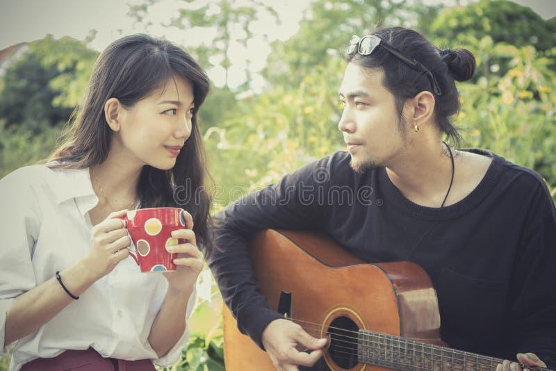 Hombre más joven asiático y mujer que tocan la guitarra con emotio de la felicidad fotos de archivo