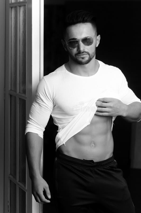 Hombre machista en las gafas de sol y la ropa de deportes que muestran el vientre muscular imagen de archivo