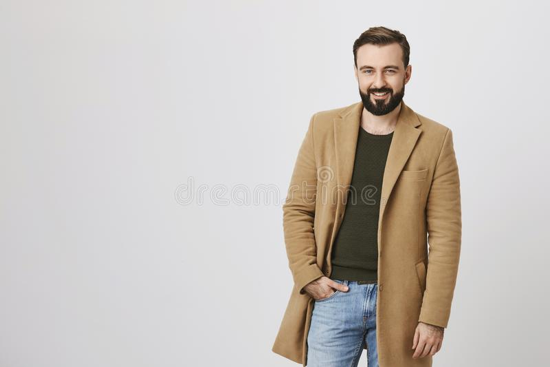 Hombre machista hermoso con la barba y bigote, capa marrón clara que lleva sobre el jersey verde, llevando a cabo la mano en vaqu fotos de archivo libres de regalías