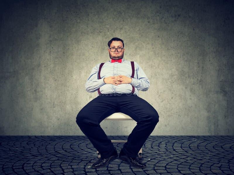 Hombre macizo perezoso que se sienta en silla imagenes de archivo