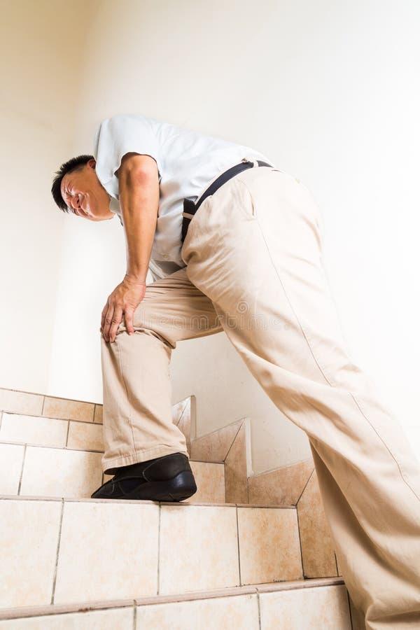 Hombre madurado que sufre las escaleras que suben agudas del dolor común de rodilla fotos de archivo