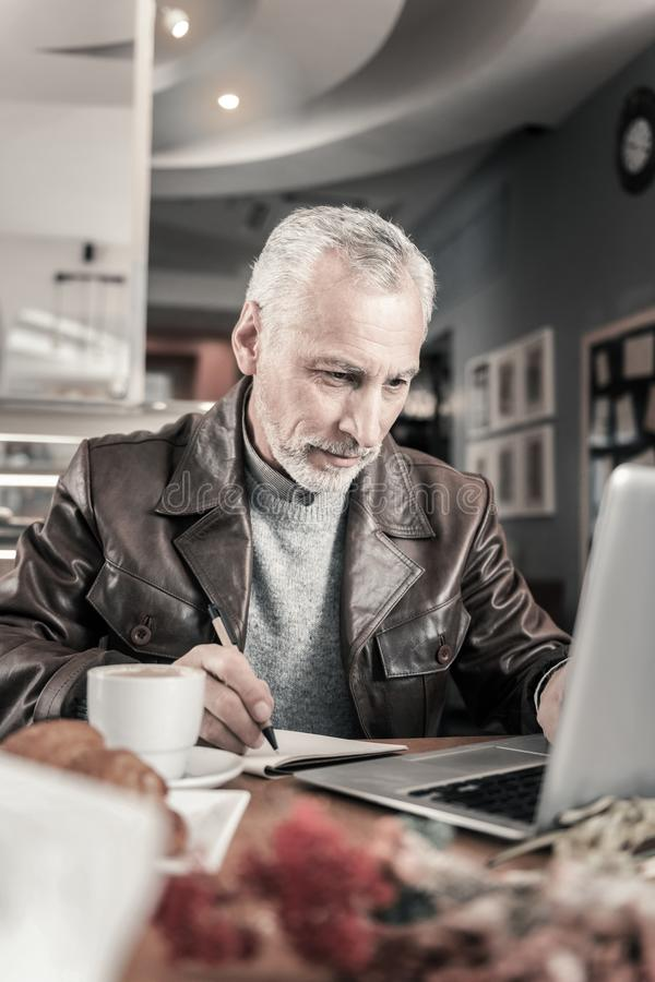 Hombre maduro alegre que trabaja en distancia en el ordenador fotos de archivo