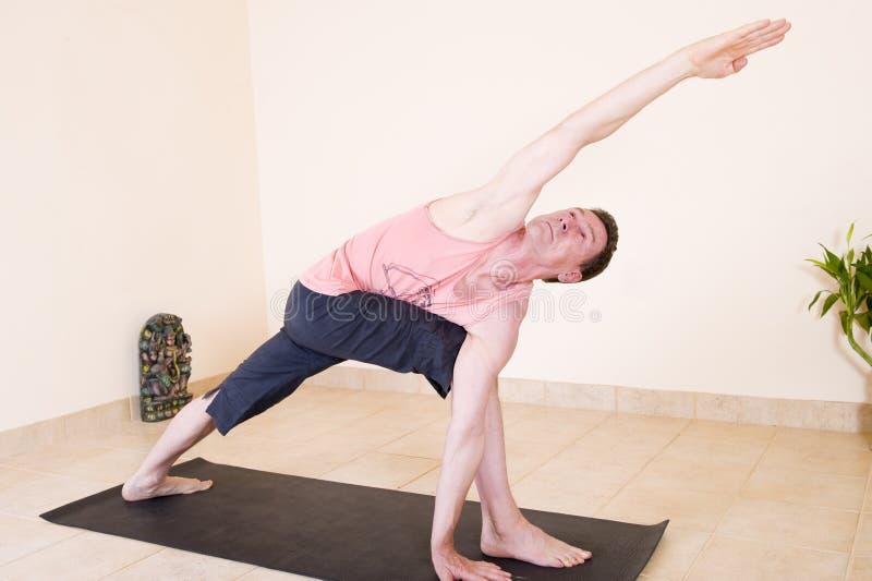 Hombre maduro atractivo que hace yoga imagenes de archivo