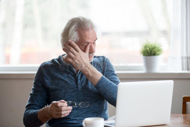 Hombre maduro cansado que saca los vidrios que sufren de ojos cansados imagen de archivo libre de regalías