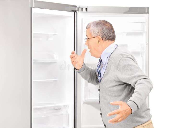 Hombre maduro chocado que mira en refrigerador vacío fotografía de archivo
