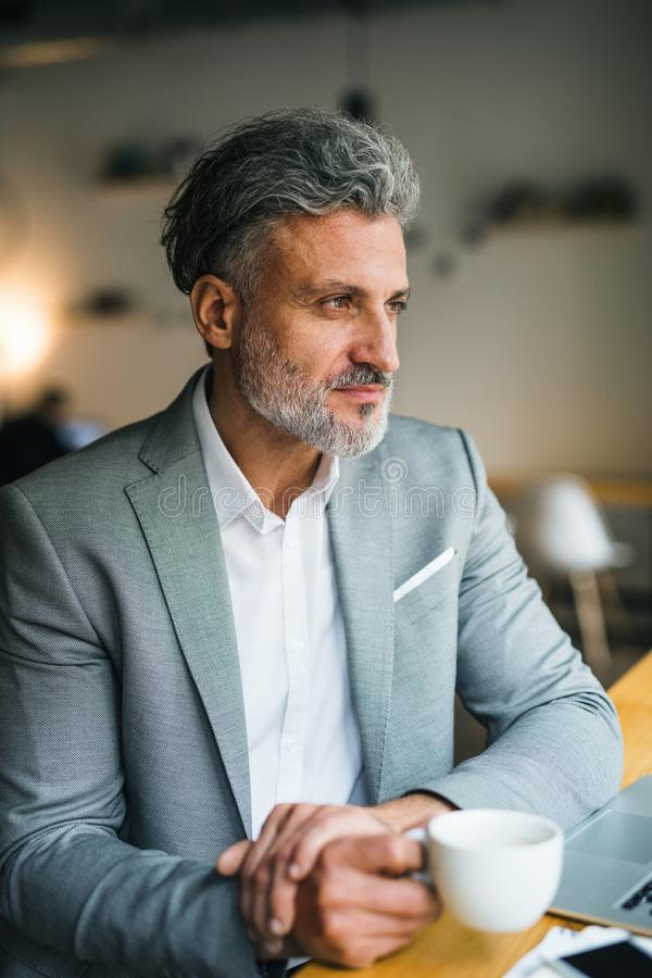 Hombre maduro con café en la tabla en un café, mirando fuera de ventana fotografía de archivo libre de regalías