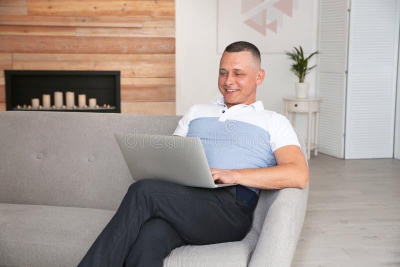 Hombre maduro con el ordenador port?til que se sienta en el sof? imagen de archivo libre de regalías